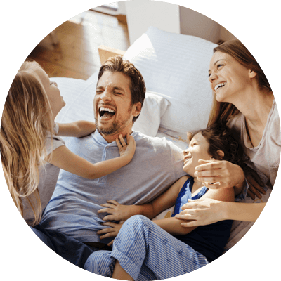 Family laughing on bed