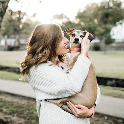 woman carries her dog