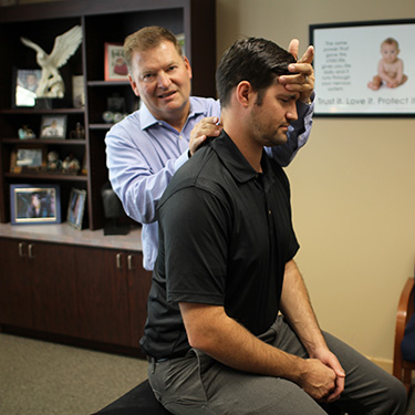 Dr. Stuckey checking the neck position of a chiropractic patient.