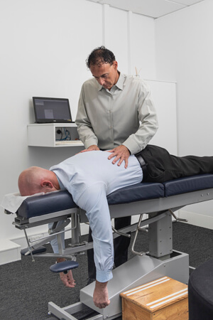 Dr Zuckerman examines male patient on adjusting table