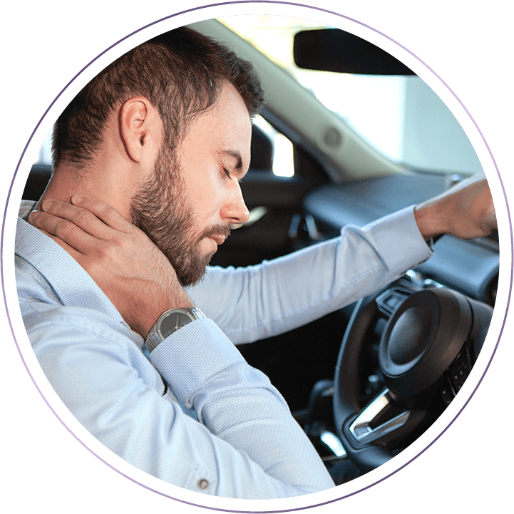 man sitting in car holding neck