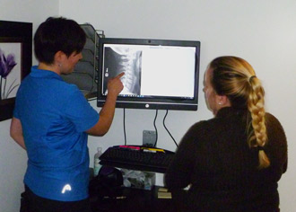 Dr. Eve explains xray results to chiropractic patient.