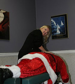 Santa gets adjusted by Dr. Claire, Roswell Chiropractor at Care-More Chiropractic!