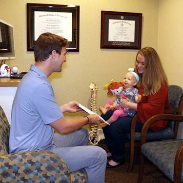 Doctor reviewing results with woman and her baby