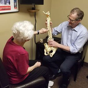 Patient and doctor looking at spine model