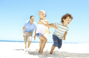 Family playing playing and running on the beach