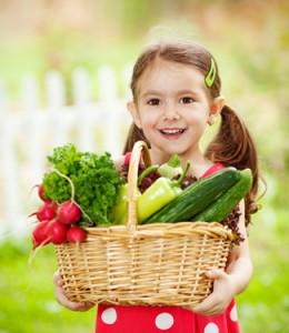 Little girl holding a basket of fresh veggies.