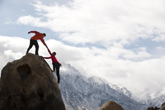 Two people climbing to the top of a mountain together