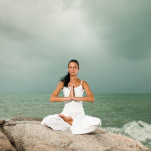 women sitting in a yoga pose on rocks by the sea