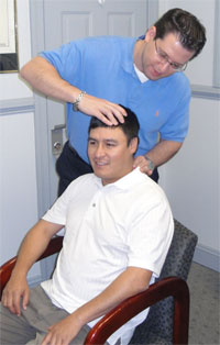 Dr. Tas ready to administer a gentle cervical adjustment.