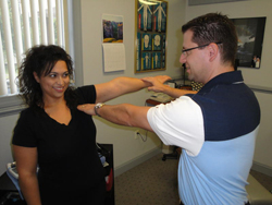 The doctor is gently muscle testing the patient.