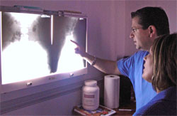 Dr. Anastasios Hatzakos reviewing x-rays with a patient.