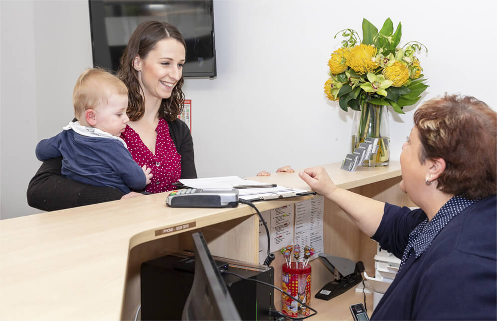 Woman holding baby at front desk