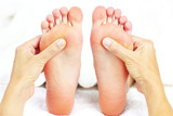 Photo of feet and reflexology therapy being performed.