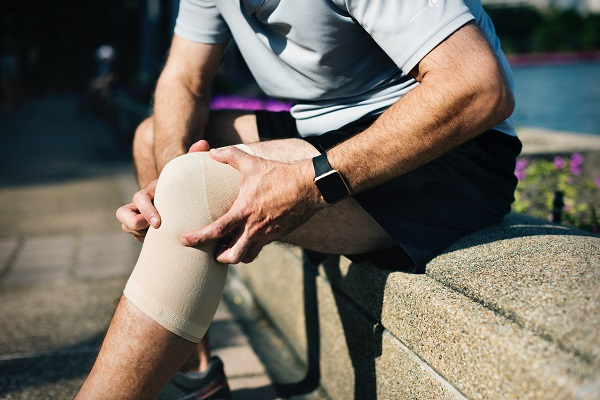 Man holding bandaged knee out in sunshine