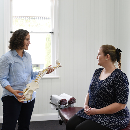 chiropractor consulting with a pregnant patient