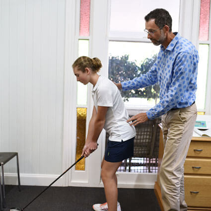 Chiro with client evaluating golf swing