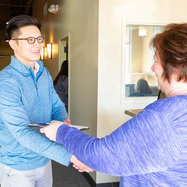 Patient handing paperwork to Dr. Tran