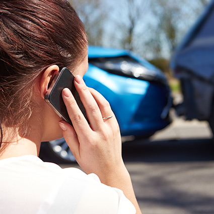 woman on her cell phone after an auto accident