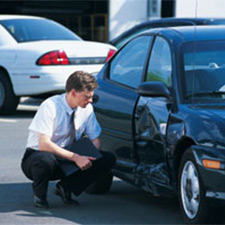man looking at dented car door from car accident
