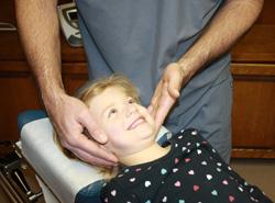 Chiropractor adjusting child