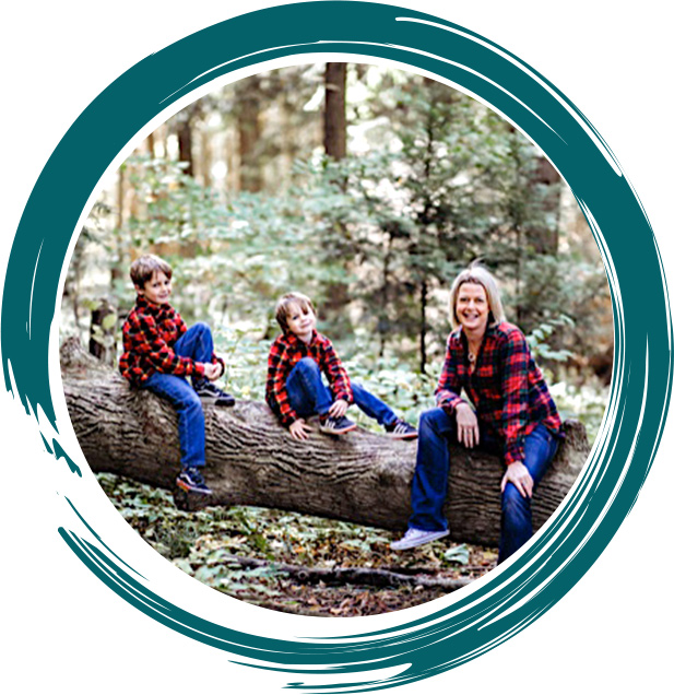 Dr. Lindsey and sons sitting on log outdoors