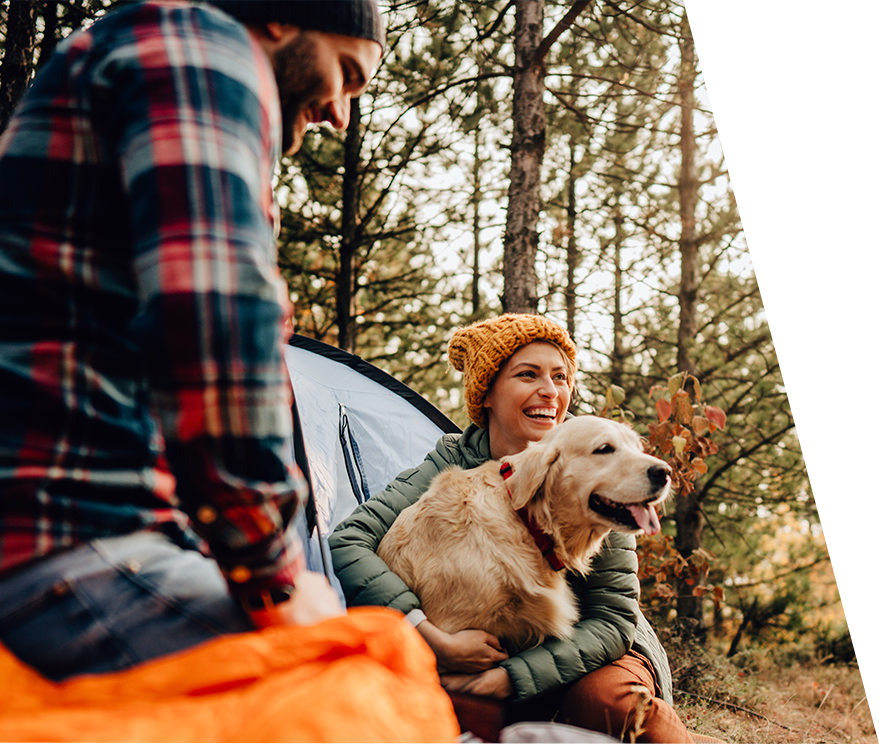 woman holding dog while camping