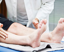 Doctor touching womans feet