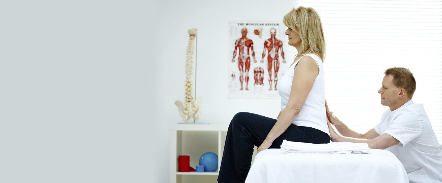 Doctor adjusting woman sitting