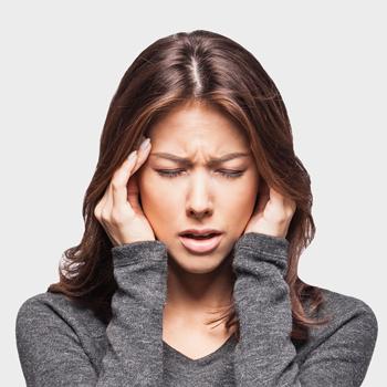 woman grabbing head in pain