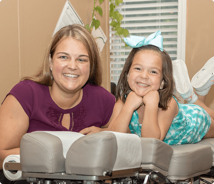 Little girl laying smiling on table with mom next to her