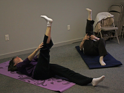 Photo of people stretching on the floor mats