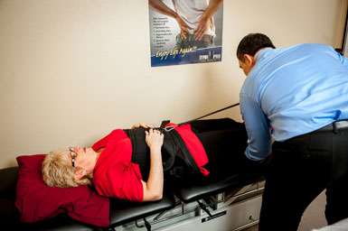Dr. Johnson putting patient on spinal decompression table