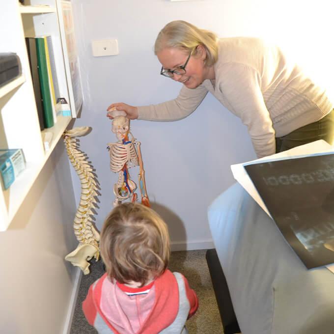 Dr. Kathy holding skeleton model for child