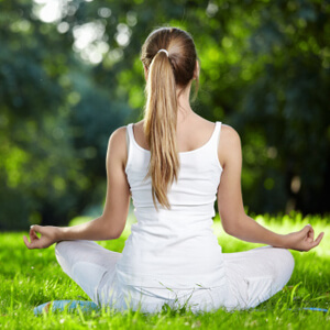 Woman seated in grass meditating