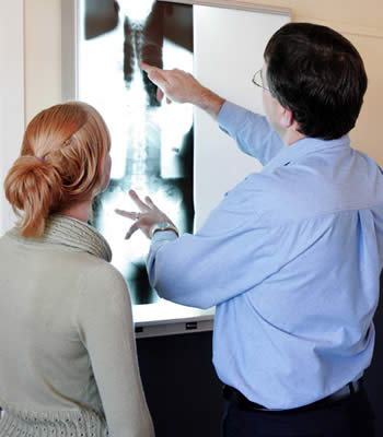 Chiropractor explaining x-rays to patient