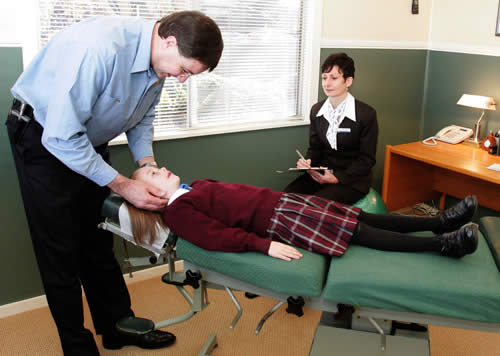 Chiropractor adjusting young child