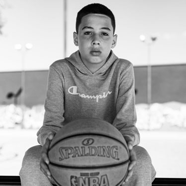kid sitting on bench holding a basketball