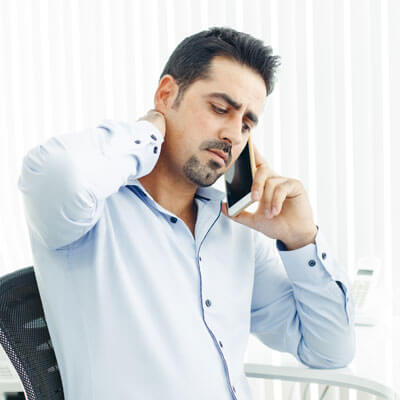 man with neck pain on phone