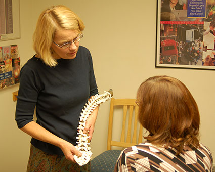 Dr. Helen showing spine model to patient