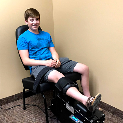 Boy knee strapped in chair