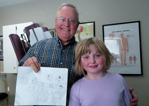Dr. Braun with a chiro kid holding up the drawing she made