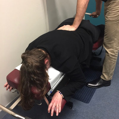 Doctor adjusting a patient on chiropractic table