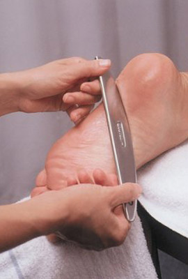 GT-4 Instrument pictured treating a patient's plantar fascia