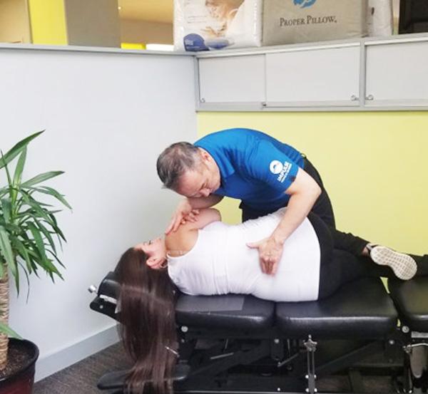Doctor adjusting woman's back