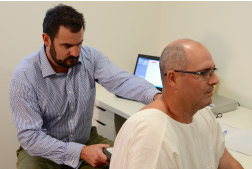 Dr Peter  conducting a scan on a new patient to objectively determine how his spine  is functioning