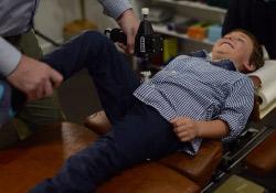 Dr Peter gently adjusting a young boy's pelvis