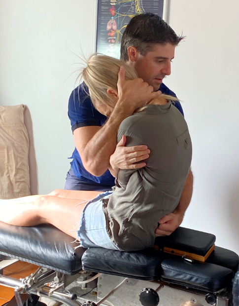 Dr. Clay adjusting woman sitting on table