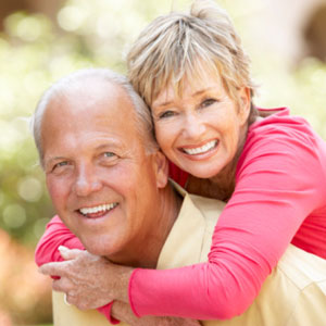 Older couple smiling and hugging outdoors.