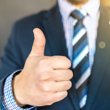 man wearing coat and tie thumbs up